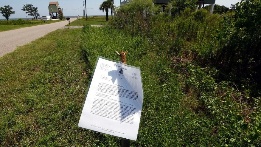 In this July 24, 2015 photograph, an order to clean up the deserted lot is posted along South Seashore Avenue in Long Beach, Miss. The city has worked to keep lots from getting overgrown, cutting vegetation on some lots and then attaching it to an owner's tax bill. Now, the city is following the lead of some Mississippi coast neighbors by requiring owners to remove remaining slabs from destroyed structures. Neighborhood resident and Long Beach alderman Gary Ponthiuex believes cleaning up the lots will help sell the property and promote home building. (AP Photo/Rogelio V. Solis)