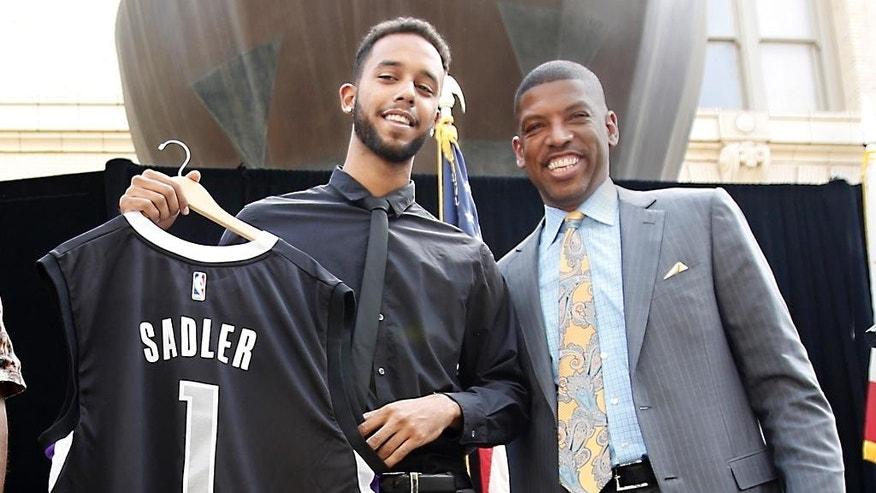 "Anthony Sadler, one of the three Americans that helped stop an alleged terrorist shooting aboard a Paris bound train, displays a Sacramento Kings jersey with his name and number presented to him by Mayor Kevin Johnson at a news conference Wednesday, Aug. 26, 2015, in Sacramento,Calif.  Salder spoke briefly saying it has been a ""crazy last few days.""(AP Photo/Rich Pedroncelli)"