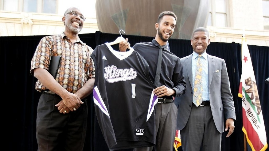 "Anthony Sadler, center, one of the three Americans that helped stop an alleged terrorist shooting aboard a Paris bound train, displays a Sacramento Kings jersey presented to him by Mayor Kevin Johnson at a news conference, Wednesday, Aug. 26, 2015, in Sacramento,Calif. Sadler, who was accompanied by his father, Anthony,, said it has been a ""crazy last few days."" (AP Photo/Rich Pedroncelli)"