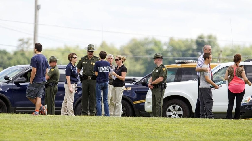 "West Virginia Police and school officials help parents reunite with their children at Philip Barbour High School following a ""hostage-type situation"" Tuesday, Aug. 25, 2015, in Philippi, W.Va. A report of someone with a gun inside the school led authorities to isolate and arrest a suspect in the building Tuesday, State Police said. (AP Photo/Ben Queen)"