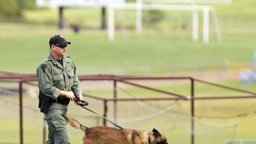 "A West Virginia Police officer and a dog walk around the perimeter of Philip Barbour High School grounds following a ""hostage-type situation"" Tuesday, Aug. 25, 2015, in Philippi, W.Va. A report of someone with a gun inside the school led authorities to isolate and arrest a suspect in the building Tuesday, State Police said. (AP Photo/Ben Queen)"