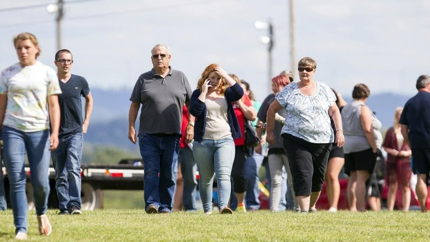 "Parents and students leave after reuniting with their children following a ""hostage-type situation"" at Philip Barbour High School, Tuesday, Aug. 25, 2015, in Philippi, W.Va. A report of someone with a gun inside the school led authorities to isolate and arrest a suspect in the building Tuesday, State Police said. (AP Photo/Ben Queen)"