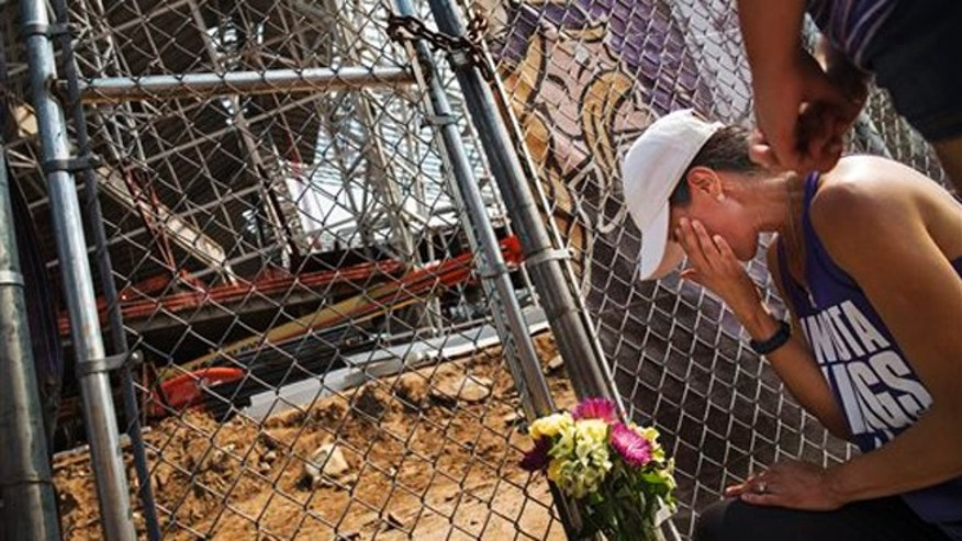 Aug. 25, 2015: Angela Strong and daughter Kyra,11, of St. Paul, Minn. leave a bouquet of flowers and say prayers for the construction workers in Minneapolis.