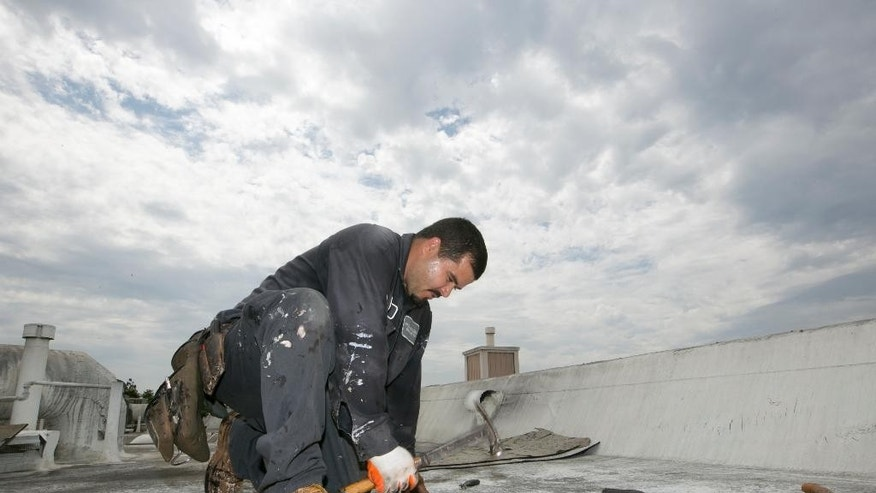 Roofer Joel Camberos with Hull Brothers Roofing & Waterproofing resurface townhomes roofs at the Marina del Rey seaside community of Los Angeles on Tuesday, Aug. 25, 2015. Roofers are reveling in the uptick in business as homeowners ready for the prospect of downpours after four years of dry weather. (AP Photo/Damian Dovarganes)