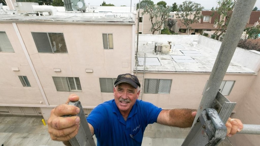 Roofer Chuck Jewett with Hull Brothers Roofing & Waterproofing climbs a ladder to check on his workers' progress resurfacing the roof of townhomes at the Marina del Rey seaside community of Los Angeles on Tuesday, Aug. 25, 2015. While drought-plagued California is eager for rain, the forecast of a potentially Godzilla-like El Nino event has communities clearing out debris basins, urging residents to stock up on emergency supplies and even talking about how a deluge could affect the 50th Super Bowl. (AP Photo/Damian Dovarganes)