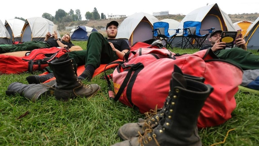 Mac Mega, center, rests with fellow firefighters from Oregon-based Grayback Forestery, at a camp for firefighters battling the Okanogan Complex Fire in Okanogan, Wash., Tuesday, Aug. 25, 2015. The firefighters were resting before their first day fighting fires in Washington state after battling blazes in California for the past three weeks, and they were sleeping in the open because they were expecting to move to a different camp on Wednesday. (AP Photo/Ted S. Warren)