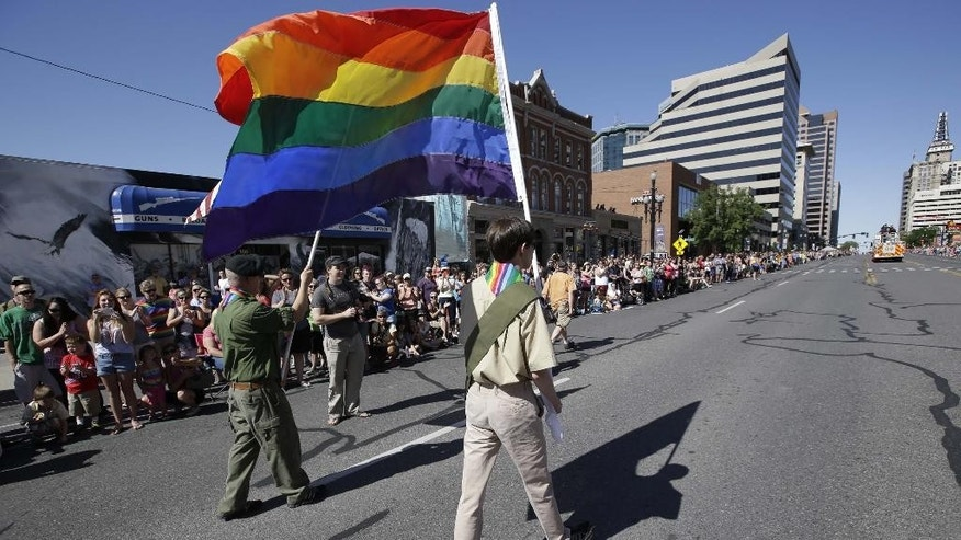 FILE - In this June 8, 2014, file photo, a group of Boy Scouts march during the Salt Lake City's annual gay pride parade, in Salt Lake City. The Mormon church, the nation's largest sponsor of Boy Scout units, is keeping its longtime affiliation with the organization despite its decision to allow gay troop leaders. Church leaders decided to stay with the Boy Scouts after getting assurances they can appoint troop leaders according to their own religious and moral values, The Church of Jesus Christ of Latter-day Saints said in a news release Wednesday, Aug. 26, 2015. (AP Photo/Rick Bowmer, File)