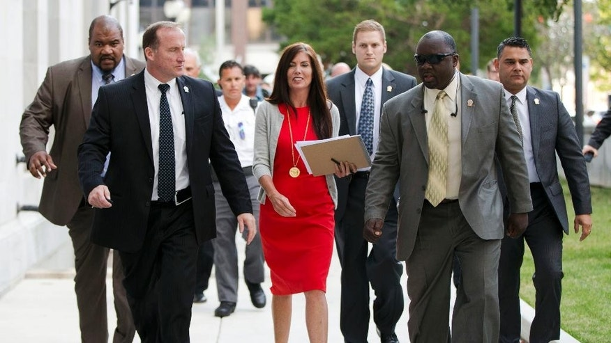 Pennsylvania Attorney General Kathleen Kane, center, departs after her preliminary hearing Monday, Aug. 24, 2015, at the Montgomery County courthouse in Norristown, Pa. Kane is accused of leaking secret grand jury information to the press, lying under oath and ordering aides to illegally snoop through computer files to keep tabs on an investigation into the leak. (AP Photo/Matt Rourke)