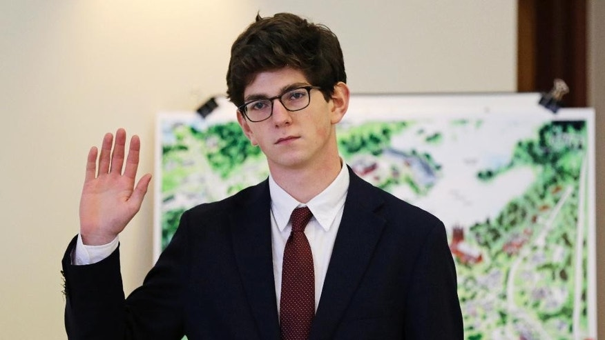 Former St. Paul's School student Owen Labrie raises his hand as he is sworn-in prior to testifying in his trial at Merrimack Superior Court in Concord, N.H., Wednesday, Aug. 26, 2015. Labrie is charged with raping a 15-year-old freshman as part of Senior Salute, in which seniors try to romance and have intercourse with underclassmen before leaving the prestigious school in Concord. The defense contends the two had consensual sexual contact but not intercourse. (AP Photo/Charles Krupa, Pool)