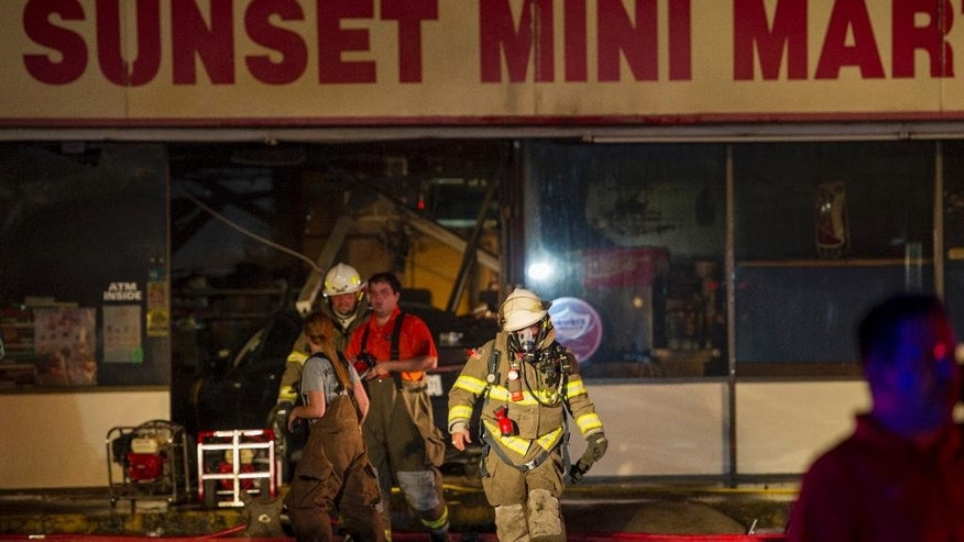 Firefighters work on the scene at the Sunset Mini Mart convenience store in Sunset, La., where a standoff with police occurred Wednesday, Aug. 26, 2015. A man barricaded himself in the store following a fatal incident. (Paul Kieu/The Daily Advertiser via AP)  NO SALES; MANDATORY CREDIT