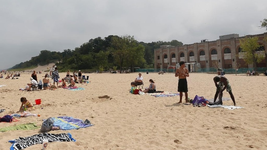 In this Aug. 10, 2015, photo, visitors relax at The Dunes State Park pavilion beach front in Chesterton, Ind. A deal with investors to privatize and refurbish the pavilion, an aging-yet-iconic structure with sweeping views of Lake Michigan, is raising questions about the privatization of public resources. (AP Photo/Christian K. Lee)