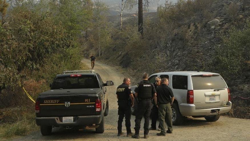 FILE -  In this Thursday, Aug. 20, 2015, file photo, Okanogan County Sheriff's deputies guard the entrance to Woods Canyon Road near Twisp, Wash. Three firefighters were killed after their engine rushed up a steep gravel road and crashed down a 40-foot embankment near the mountain town of Twisp. Before they could escape, they were overrun by flames. (AP Photo/Ted S. Warren, File)