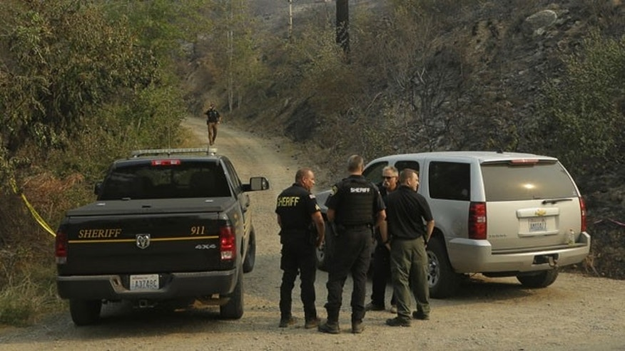 FILE -  In this Thursday, Aug. 20, 2015, file photo, Okanogan County Sheriff's deputies guard the entrance to Woods Canyon Road near Twisp, Wash. (AP Photo/Ted S. Warren, File)