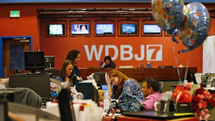 Members of the WDBJ-TV7 news staff prepare for the early morning newscast at the station, in Roanoke, Va., Thursday, Aug. 27, 2015. A reporter and cameraman from the station were killed during a live broadcast Wednesday, by a former colleague. (AP Photo/Steve Helber)