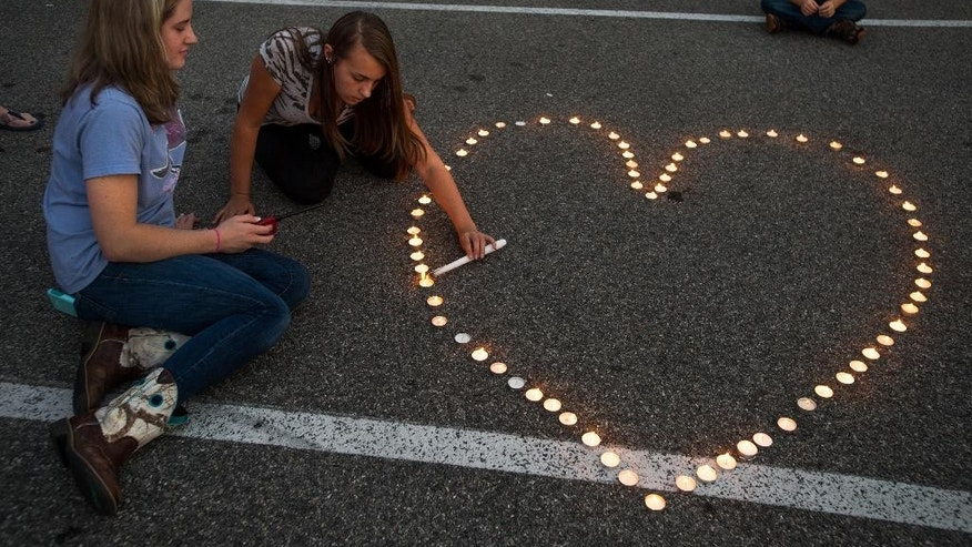 Community supporters light candles in the shape of a heart during a vigil for journalists Alison Parker and Adam Ward who were killed during a shooting in Moneta, Va., Wednesday, Aug. 26, 2015. Vester Lee Flanagan opened fire during a live on-air interview for WDBJ7, killing the two journalists Wednesday. (Autumn Parry/The News & Advance via AP)