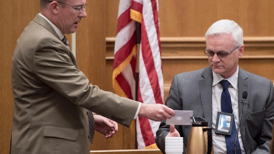 Johnson County District Attorney Steve Howe, left, hands a CD containing phone conversations of Frazier Glenn Miller Jr. to Overland Park Detective Gary Borstelman after a recording of Miller's jailhouse confession was played during Miller's capital murder trial in the Johnson County Courthouse on Thursday, Aug. 27, 2015, in Olathe, Kansas. Miller is charged with the April 13, 2014 shooting deaths of three people outside of  Overland Park Jewish facilities  in suburban Kansas City.  (Shane Keyser /The Kansas City Star via AP, Pool)