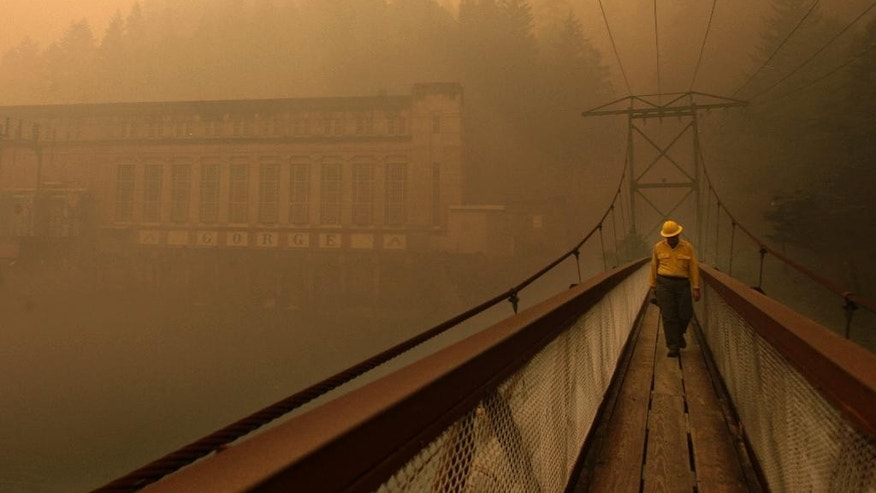 Dennis Godfrey, with the Great Basin Incident Management Team 4, walks across a bridge from the Gorge Powerhouse, Wednesday, Aug. 26, 2015, near Newhalem, Wash. Smoky conditions grounded helicopters and airplanes Wednesday that had been fighting the fires. (Mark Mulligan/The Herald via AP) MANDATORY CREDIT