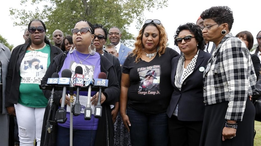 Airickca Gordon Taylor, second from left, cousin to Emmett Till and Co-Founder of the Mamie Till Mobley Memorial Foundation, addresses the crowd gathered at a gravesite ceremony at the Burr Oak Cemetery marking the 60th anniversary of the murder of Till in Mississippi, Friday, Aug. 28, 2015, in Alsip, Ill. Standing with Taylor are, Jackie Johnson, left, mother of Kendrick Johnson, Geneva Reed-Veal, mother of Sandra Bland, right, Kadiatou Diallo, mother of Amadou Diallo, second from right, and Calandrian Kemp, mothers of George Kemp Jr., third from right. (AP Photo/Charles Rex Arbogast)