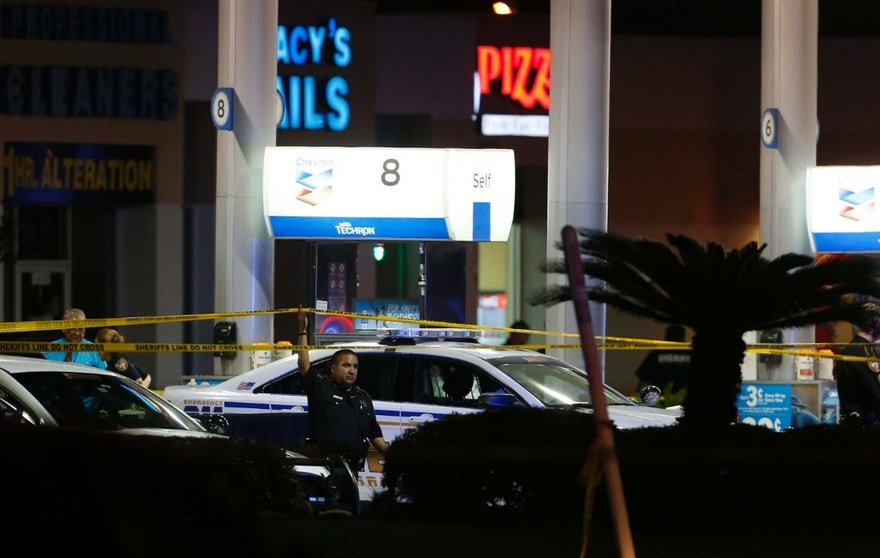 Aug. 28, 2015: Officials investigate the scene at a gas station where a sheriff's deputy in uniform was fatally shot in Houston.