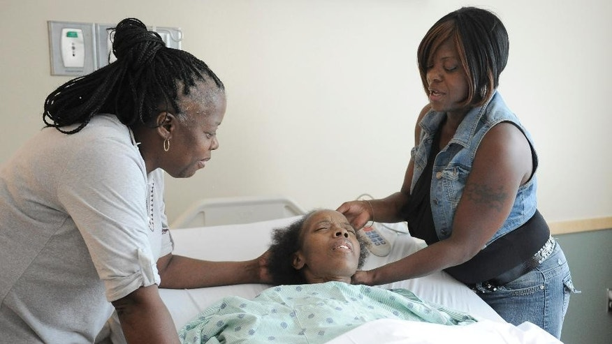 "Sisters Chevelle, left, and Champernell Washington tend to their sister Chelette Price in her hospital room in Houston on Thursday, Aug. 13, 2015. An estimated 1.5 million Gulf Coast residents fled Hurricane Katrina. Many thousands of them, like Chevelle, have taken root where they landed. But a decade after the storm, she cannot quite bring herself to call Houston ""home."" Still, with two sisters living just a couple of miles away, and the occasional New Orleans-style ""po boy"" from her resettled brother's nearby sandwich shop, it's as close to it as she can imagine. (AP Photo/Pat Sullivan)"