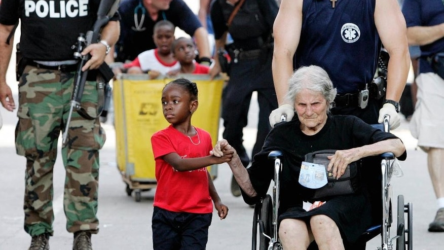 "FILE - In this Sept. 3, 2005 file photo, Tanisha Blevin, 5, holds the hand of fellow Hurricane Katrina victim Nita LaGarde, 105, as they are evacuated from the convention center in New Orleans. Photographer Eric Gay recalled, ""It was a sweet moment. Kind of uplifting despite the whole ordeal."" (AP Photo/Eric Gay, File)"