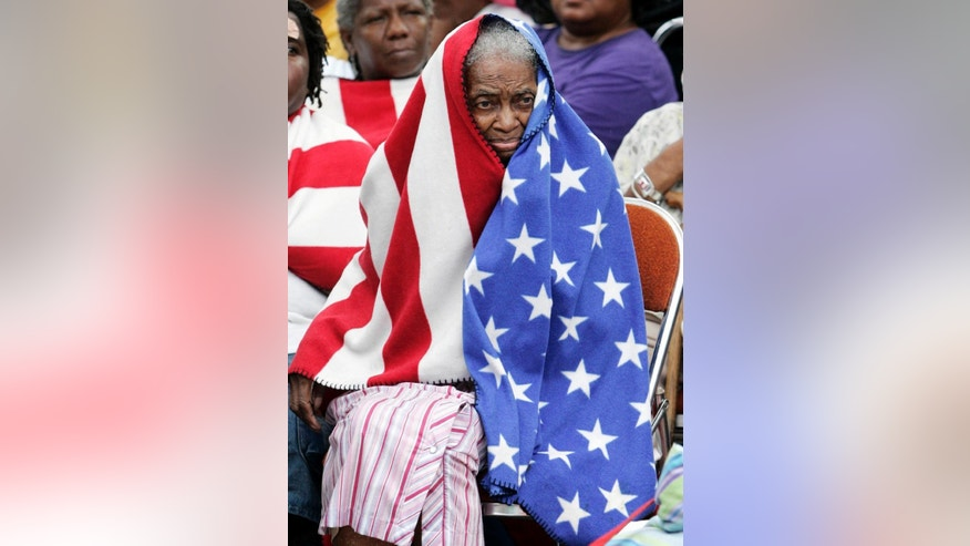 "FILE - In this Thursday, Sept. 1, 2005 file photo, Milvertha Hendricks, 84, covered with a blanket depicting an American flag, waits in the rain with other flood victims outside the convention center in New Orleans. When taking the photo, photographer Eric Gay recalls, ""I'm always a sucker for flags. But it wasn't only that. It was the pathos in their faces. They looked so despondent. It just was not a good situation."" (AP Photo/Eric Gay, File)"