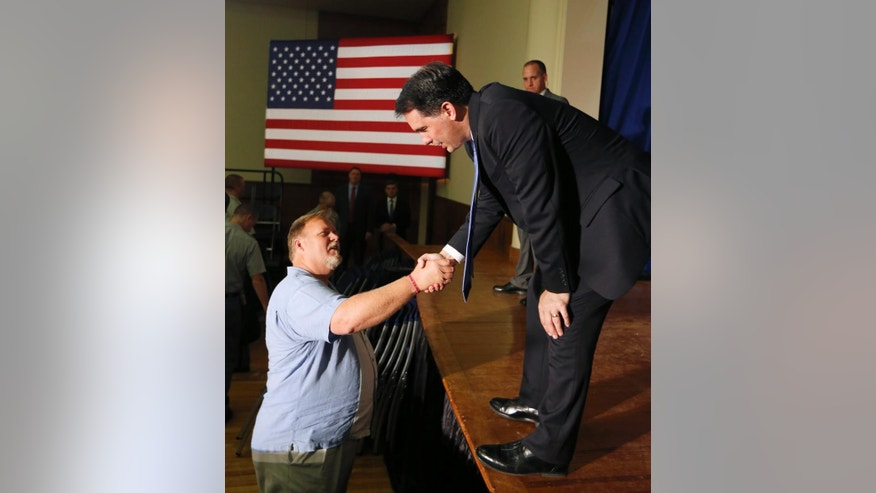 Republican presidential candidate, Wisconsin Gov. Scott Walker, right, shakes hands with John A. Steward III of from Monroe, N.C., after delivering a foreign policy speech on the campus of The Citadel, Friday, Aug. 28, 2015, in Charleston, S.C. (AP Photo/Mic Smith)
