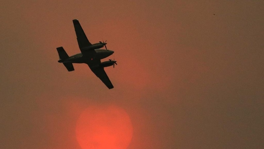 An airplane used to fight wildfires flies past the sun, which appears orange due to heavy smoke in the air while battling a blaze that flared up in the late afternoon near Omak, Wash., Thursday, Aug. 27, 2015. Firefighters were holding their own Thursday against the largest wildfire on record in Washington state, even as rising temperatures and increased winds stoked the flames. (AP Photo/Ted S. Warren)