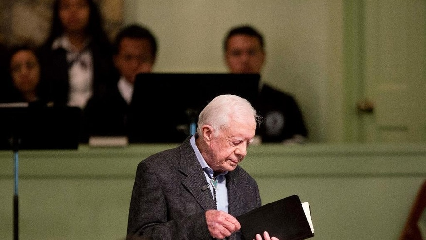 FILE - In this Aug. 23, 2015 file photo, former President Jimmy Carter opens up a Bible while teaching Sunday School class at Maranatha Baptist Church in his hometown in Plains, Ga.  Carter's recent diagnosis that cancer has spread to his brain will require him to scale back his work, but Carter Center officials say their programs will continue uninterrupted.  (AP Photo/David Goldman)