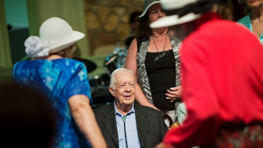 FILE - In this Aug. 23, 2015 file photo, former President Jimmy Carter, sits to pose for photos after teaching Sunday School class at Maranatha Baptist Church in his hometown in Plains, Ga.  Carter's recent diagnosis that cancer has spread to his brain will require him to scale back his work, but Carter Center officials say their programs will continue uninterrupted.  (AP Photo/David Goldman)