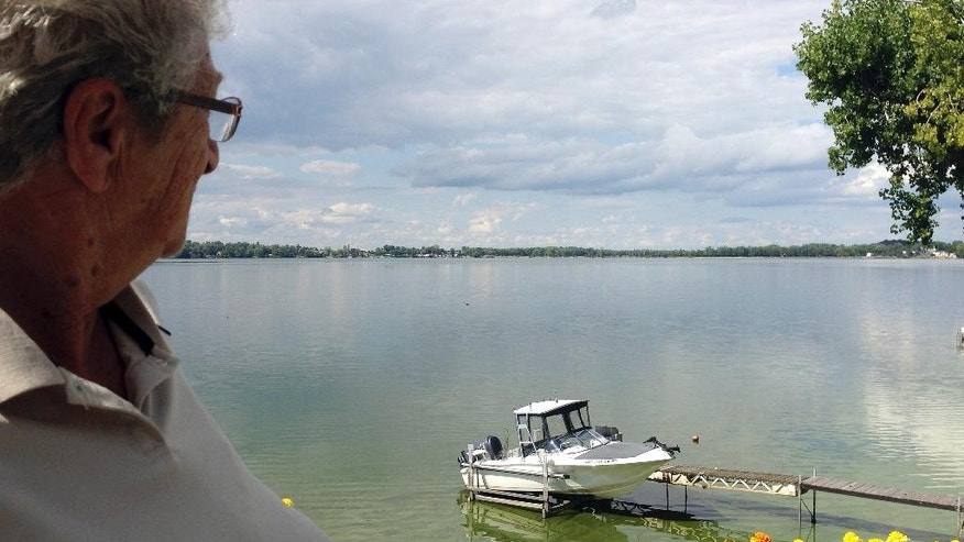 In this Wednesday, Aug. 26, 2015 photo, Enid Letourneau looks from the deck of her cottage in Georgia, Vt., at the blue-green algae in St. Albans Bay on Lake Champlain. The town recently reduced the value of 34 homes along the shore by $50,000 each because of the algae, which can be toxic to humans and dogs. (AP Photo/Lisa  Rathke)