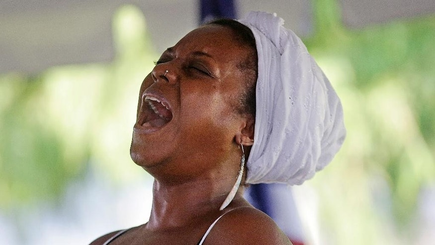 Michaela Harrison sings a gospel hymn at a wreath laying ceremony at the Hurricane Katrina Memorial, on the 10th anniversary of Hurricane Katrina in New Orleans, Saturday, Aug. 29, 2015. (AP Photo/Gerald Herbert)