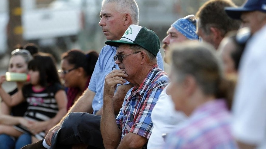 In this July 1, 2015 photo, Jeff Smith, center, listens with other members of the community of Okieville as they meet to hear plans on confronting the drought on the outskirts of Tulare, Calif. As more wells run dry in Okieville, a growing concern is uniting neighbors on the idea something must be done. (AP Photo/Gregory Bull)