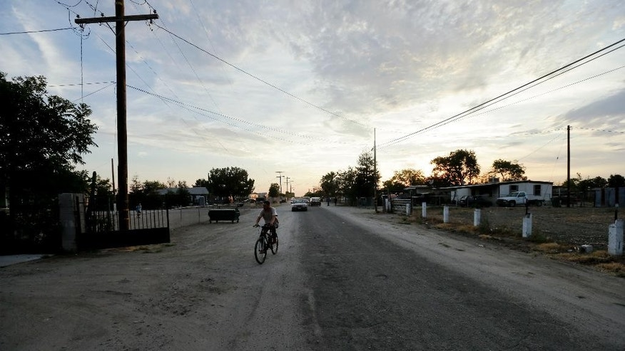 In this July 2, 2015 photo, a man rides a bike down one of the dirt roads of the community of Okieville, on the outskirts of Tulare, Calif. Here, 100 modest homes share narrow, cracked streets without sidewalks, stop lights or streetlights in the arid southeast corner of California's Central Valley. (AP Photo/Gregory Bull)