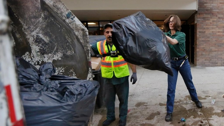 New York University professor and Department of Sanitation of New York anthropologist-in-residence Robin Nagle, right, tosses a bag of garbage into the truck as she accompanies sanitation worker Joe Damiano, during his morning rounds, Wednesday, Aug. 12, 2015, in New York. Nagle studies the refuse along the curbs of the nation's biggest city as a mirror into the lives of its 8.5 million residents. (AP Photo/Richard Drew)