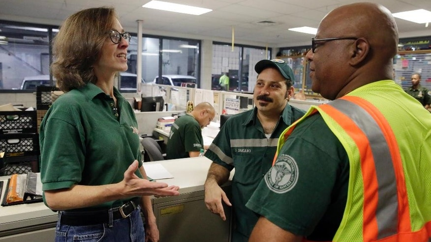 New York University professor and Department of Sanitation of New York anthropologist-in-residence Robin Nagle, left, talks with sanitation workers Joe Damiano, center, and Jose Mejia, at their garage prior to accompanying them during their morning assignment, Wednesday, Aug. 12, 2015, in New York. Nagle studies the refuse along the curbs of the nation's biggest city as a mirror into the lives of its 8.5 million residents. (AP Photo/Richard Drew)