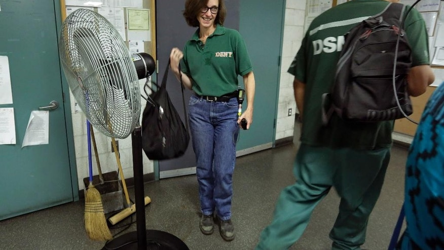 New York University professor and Department of Sanitation of New York anthropologist-in-residence Robin Nagle, left, grabs her backpack at the DSNY garage prior to accompanying sanitation workers on their morning rounds, Wednesday, Aug. 12, 2015, in New York. Nagle studies the refuse along the curbs of the nation's biggest city as a mirror into the lives of its 8.5 million residents. (AP Photo/Richard Drew)