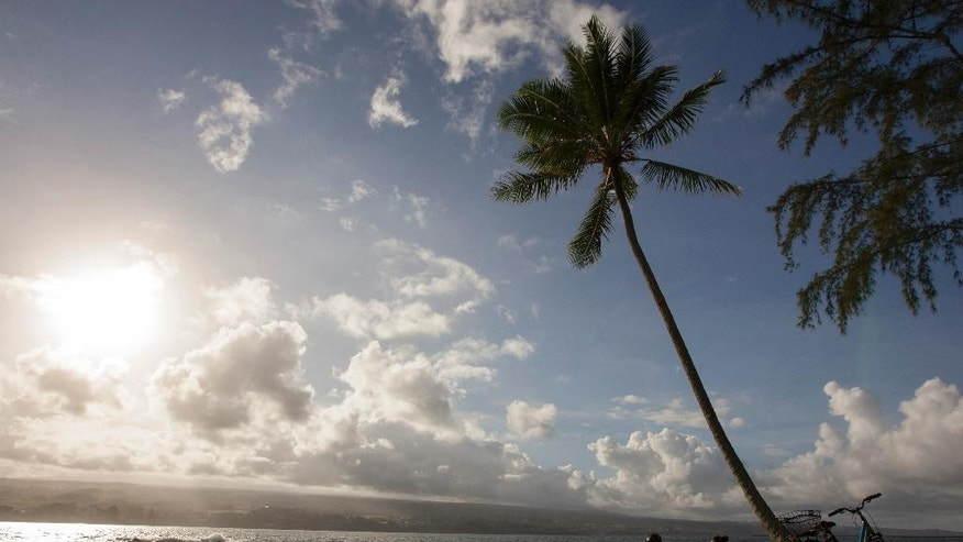 Keenin Ide, left, of Hilo, Hawaii, and Medea Yankova, of Sofia, Bulgaria, sit near Hilo Bay in Hilo Hawaii, Sunday Aug. 30, 2015. Hurricane Ignacio is forecast to weaken and move north of the Hawaiian Islands on Monday and Tuesday. (AP Photo/Caleb Jones)