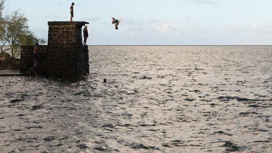 A swimmer jumps into Hilo Bay in Hilo Hawaii, Sunday Aug. 30, 2015. Hurricane Ignacio is forecast to weaken and move north of the Hawaiian Islands on Monday and Tuesday. (AP Photo/Caleb Jones)