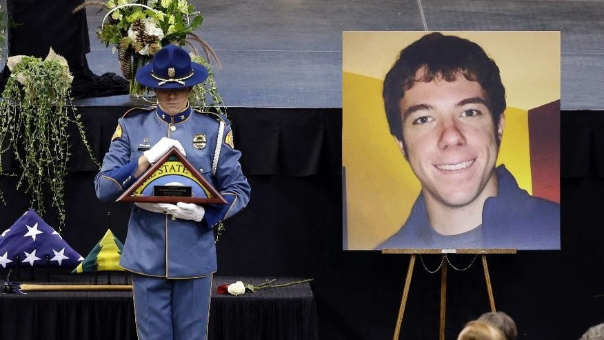 A Washington State Patrol trooper holds a state flag to be presented to the family as he stands near a portrait of Thomas Zbyszewski at a memorial service for three firefighters killed in a wildfire, Sunday, Aug. 30, 2015, in Wenatchee, Wash. Richard Wheeler, Andrew Zajac and Zbyszewski died Aug. 19 in a fire near Twisp, Wash. (AP Photo/Elaine Thompson)