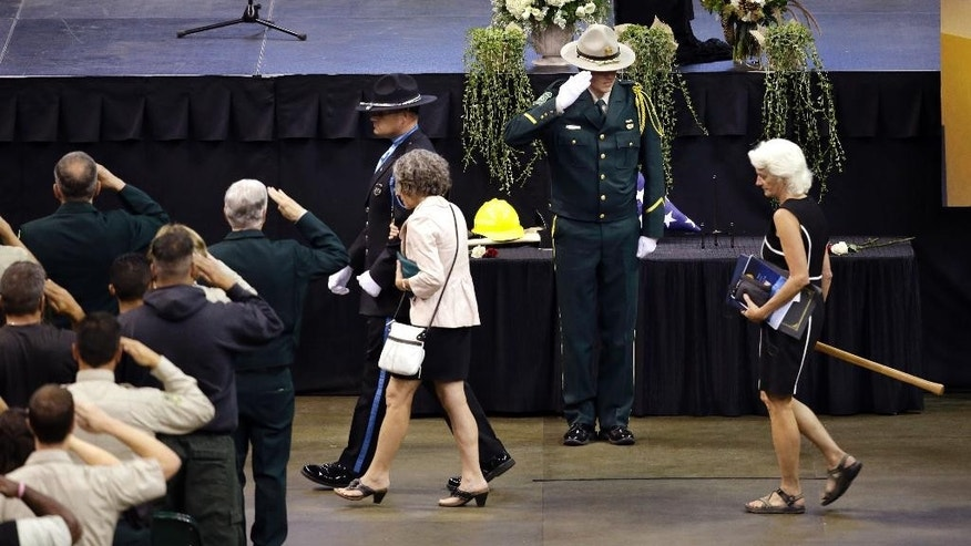 Family members, one carrying a fire tool given as a remembrance, are escorted out following a memorial service for three firefighters killed in a wildfire, Sunday, Aug. 30, 2015, in Wenatchee, Wash. Richard Wheeler, Andrew Zajac and Thomas Zbyszewski died Aug. 19 in a fire near Twisp, Wash. (AP Photo/Elaine Thompson)