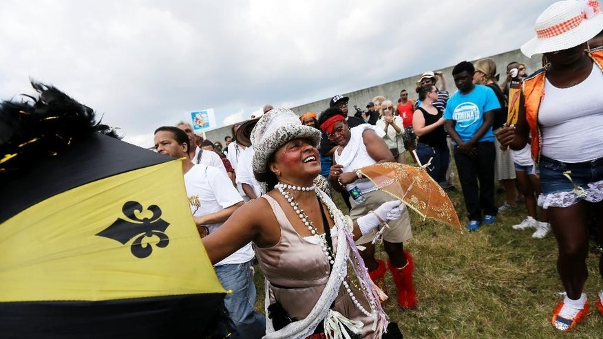 People dance in a second-line parade as it leaves the floodwall of the Industrial Canal  at the spot of the breach during Hurricane Katrina, to commemorate the 10th anniversary of the storm in the Lower 9th Ward of New Orleans, Saturday, Aug. 29, 2015. Residents in Mississippi and Louisiana were marking the somber anniversary by paying homage to those who died in Katrina, to thank those who came to rebuild and celebrate how far the region has come since the hurricane struck. (AP Photo/Gerald Herbert)