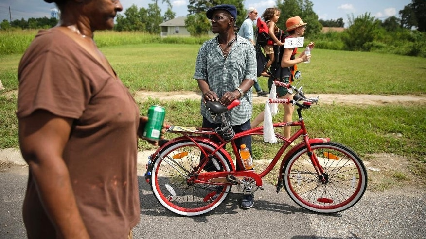 Joe Johnson watches with his bicycle as people walk with a second-line parade commemorating the 10th anniversary of Hurricane Katrina, in the Lower 9th Ward of New Orleans, Saturday, Aug. 29, 2015. Residents in Mississippi and Louisiana were marking the somber anniversary by paying homage to those who died in Katrina, to thank those who came to rebuild and celebrate how far the region has come since the hurricane struck. (AP Photo/Gerald Herbert)