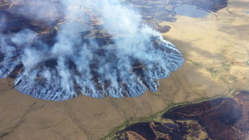 FILE - In this Sunday, June 7, 2015 file photo provided by the Alaska Division of Forestry, smoke rises from the Bogus Creek Fire, one of two fires burning in the Yukon Delta National Wildlife Refuge in southwest Alaska. Global warming is carving measurable changes into Alaska, and President Barack Obama is about to see it. President Obama leaves Monday, Aug. 31, 2015 for a three-day visit to the 49th state in which he will speak at a State Department climate change conference and become the first president to visit the Alaska Arctic. There and even in the sub-Arctic part of the state, he will see the damage caused by warming, damage that has been evident to scientists for years.  (Matt Snyder/Alaska Division of Forestry via AP, File )