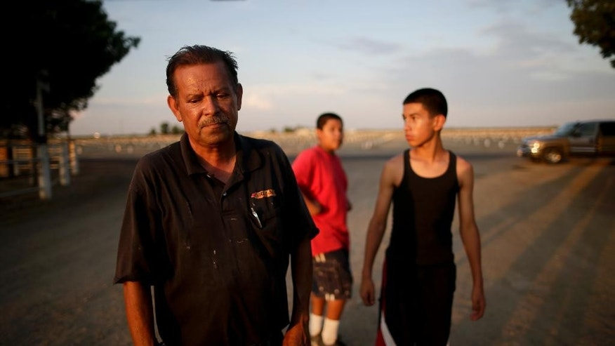 In this June 30, 2015 photo, Gilbert Arredondo, left, looks down as he talks about his town's water crisis, standing in front of his tenant's sons, in the community of Okieville, on the outskirts of Tulare, Calif. Arredondo had just informed his tenant, Tino Lozano, that the well connecting their houses had gone dry. The water is disappearing at a particularly alarming pace in their neighborhood, forcing neighbors to rig lines from house to house to share what underground water is still reachable from the deepest wells. (AP Photo/Gregory Bull)