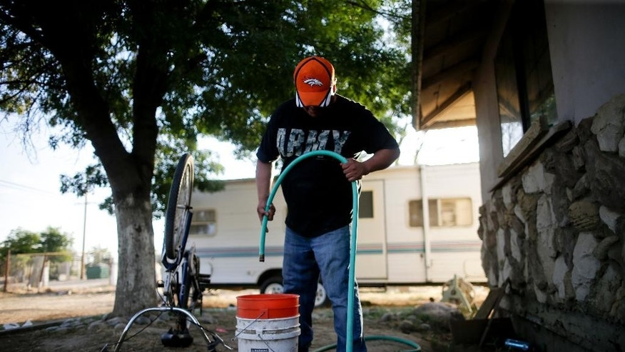 "In this June 30, 2015 photo, Tino Lozano looks into a bucket as the last of his available well water drips from a hose in front of his home in the community of Okieville, on the outskirts of Tulare, Calif. ""There it goes. That was all,"" said Lozano, masking his desperation with a smile. ""That's how we do it in Okieville now."" Millions of Californians are being inconvenienced in this fourth year of drought, but it's worse in places like Okieville, where wells have gone dry for many in the Central Valley community which was built by refugees from Oklahoma's epic Dust Bowl drought. (AP Photo/Gregory Bull)"