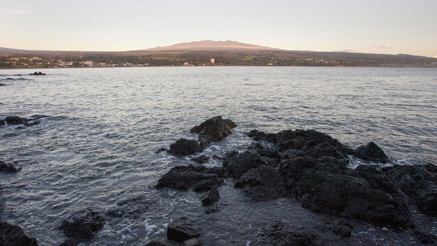 Gentle waves roll into Hilo Bay with the Big Island's Mauna Kea in the background, Monday, Aug. 31, 2015, in Hilo, Hawaii. Hurricane Ignacio is rapidly weakening and has moved farther away from the Hawaiian Islands, allowing forecasters to lift the tropical storm watches for the Big Island and Maui. (AP Photo/Caleb Jones)