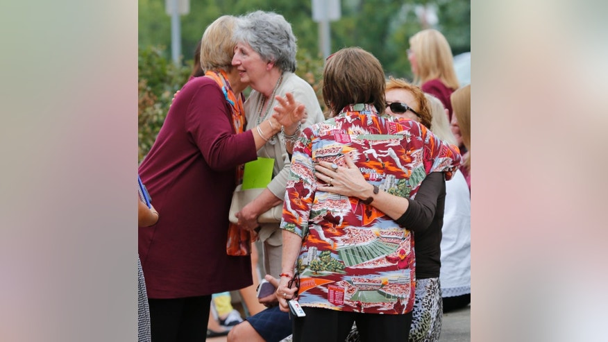 Mourners hug as they arrive at Salem High school to remember alumnus WDBJ-TV cameraman Adam Ward, in Salem, Va., Monday, Aug. 31, 2015. Ward and reporter Alison Parker were gunned down by a former co-worker during a live shot last week. Salem High School opened its doors to the community Monday to commemorate the life of alumnus Ward. (AP Photo/Steve Helber)