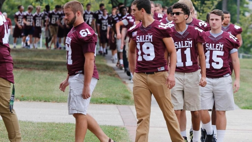 Members of the Salem High school football team arrive for a visitation for WDBJ-TV cameraman Adam Ward at the school in Salem, Va., Monday, Aug. 31, 2015. Ward and reporter Alison Parker were gunned down by a former co-worker during a live shot last week. Salem High School opened its doors to the community Monday to commemorate the life of alumnus Ward. (AP Photo/Steve Helber)