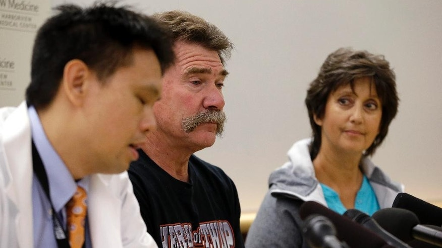 Dr. Tam Pham, left, speaks as Daniel and Barbara Lyon, parents of injured firefighter also named Daniel Lyon, listen at a news conference about their son's recovery Tuesday, Sept. 1, 2015, at Harborview Medical Center in Seattle. The younger Daniel Lyon, who was injured in a wildfire Aug. 19 near Twisp, Wash., that killed three firefighters, has undergone multiple surgeries and more are planned. (AP Photo/Elaine Thompson)